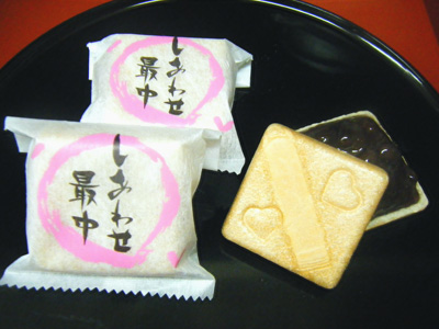 「しあわせ最中」です。 この商品は、自家製・オリジナルの商品です。 名前の由来ですが、食べて頂いたお客様が、幸せや喜びが溢れますようにと考えたお菓子です。 こだわりの最中の皮 最中の皮は、厳選したもち米を使ってこんがり香ばしく焼いております。 中身は、仕込みに4日以上かけてじっくり丁寧に作っております。 自慢の餡 特徴として、いつも 食べているの最中とは、違います。 それは、甘さをあまり感じることなく、深みがありすぐ食べてしまうような感じです。